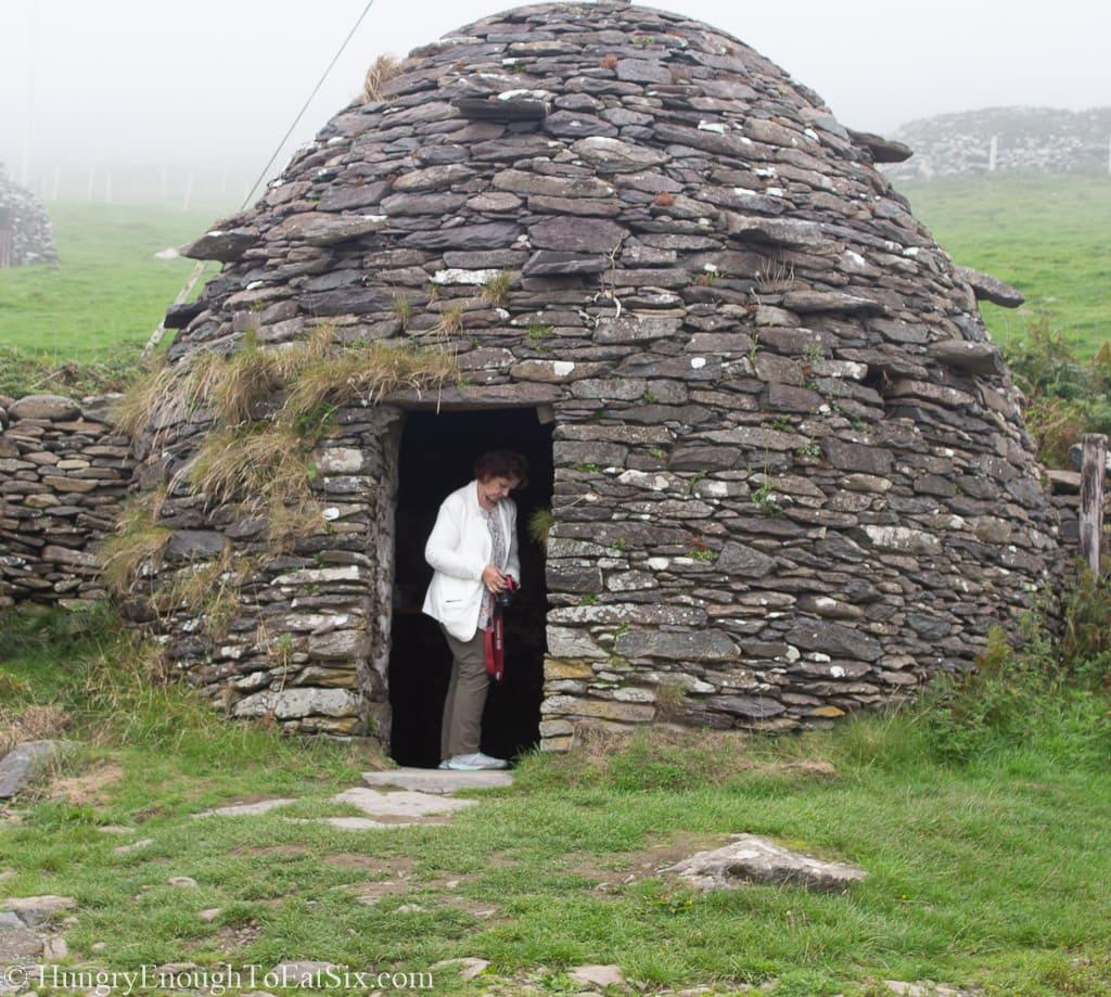 Woman in doorway of stone hut