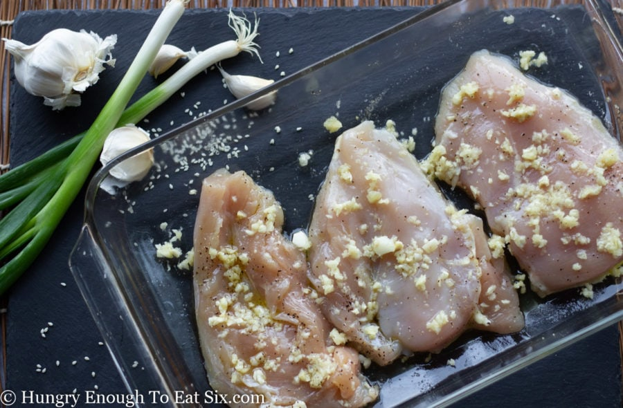 Raw chicken breast in a baking dish with chopped garlic.