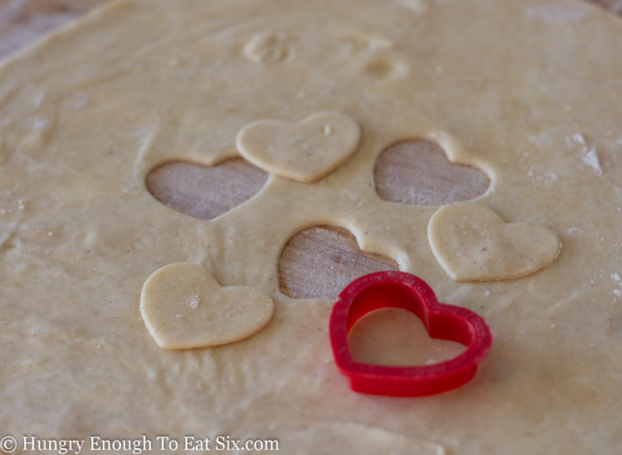 Heart cutouts from pie crust dough and red heart cookie cutter