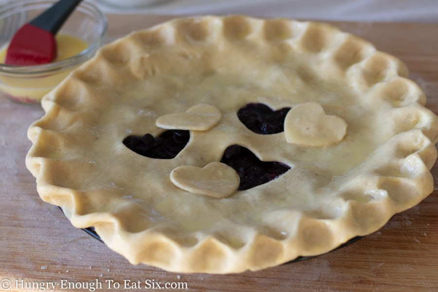 Unbaked blueberry pie with heart cutouts and egg wash.