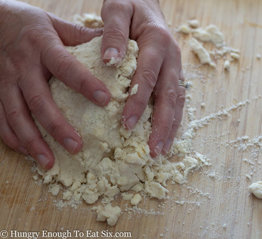 Floury dough ingredients being gathered between two hands on cutting board