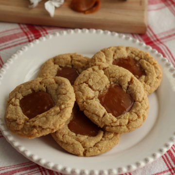 White plate with five peanut butter cookies