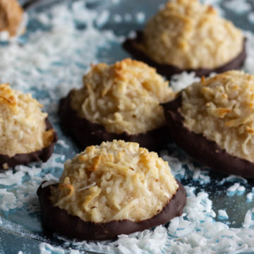Coconut scattered over blue plate holding macaroons