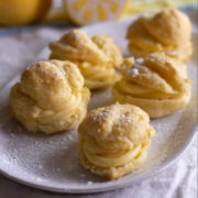 Cream puffs with yellow lemon filling on a white plate.