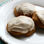 White plate with brown cookies topped with frosting
