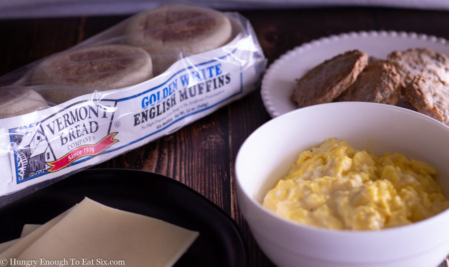 English muffins, sausage patties and a bowl of scrambled eggs.