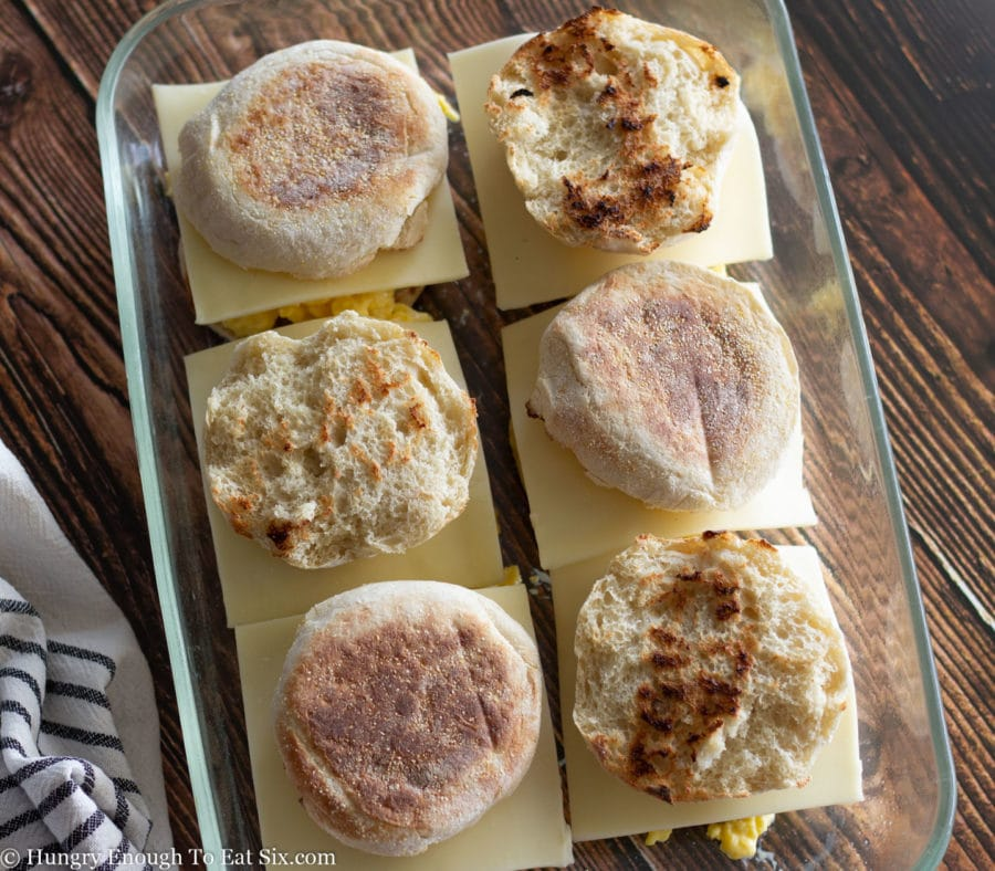 Toasted English muffin tops on breakfast sandwiches in a pan.