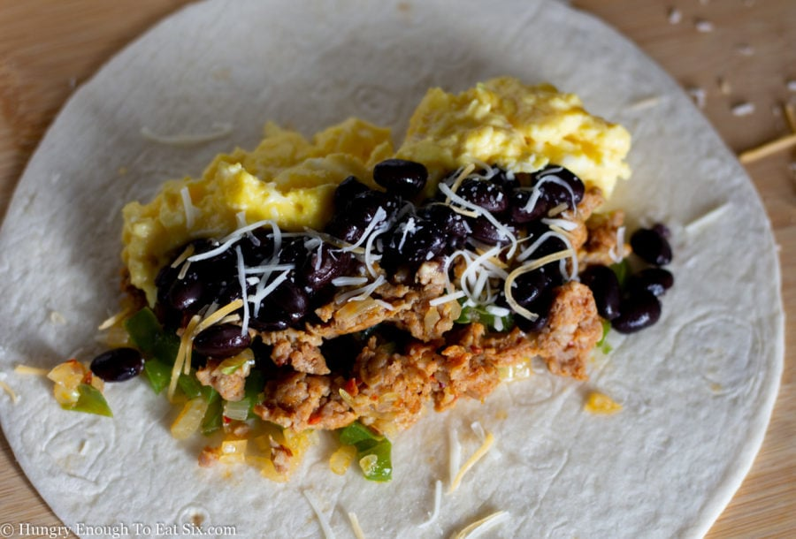 Sausage, egg and black beans on a flour tortilla.