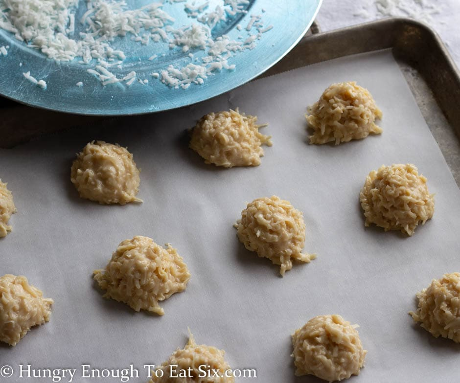 Scoops of macaroon batter on a lined baking sheet