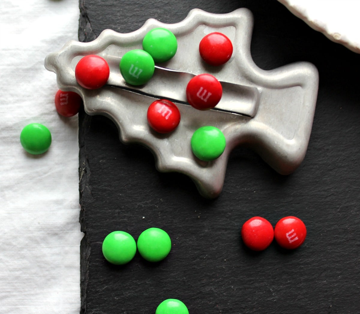 Red and green M&M's with a metal Christmas tree cookie cutter.