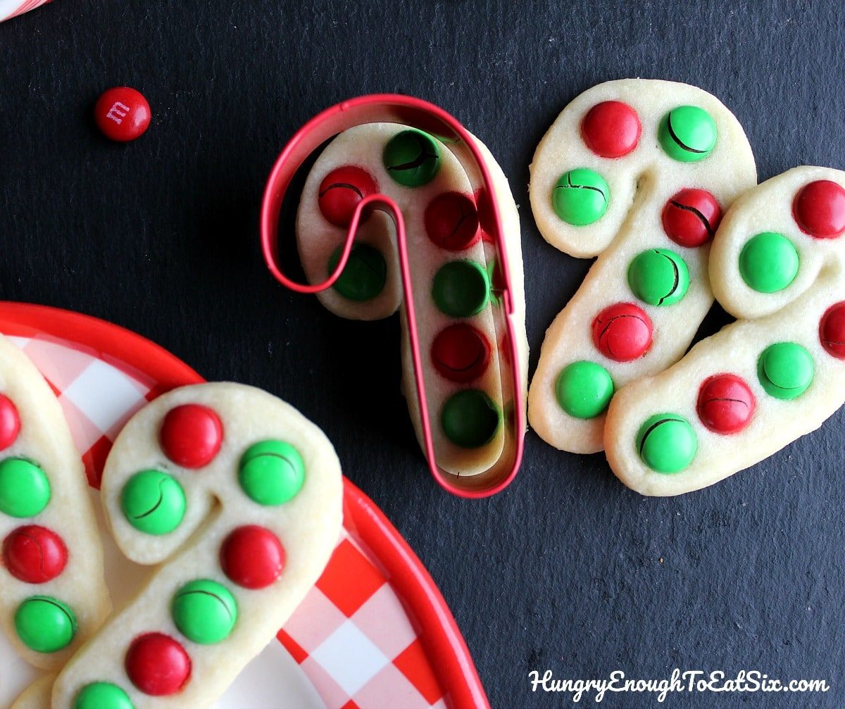 Candy cane shaped cookies with red and green M&M's and a red candy cane cookie cutter.