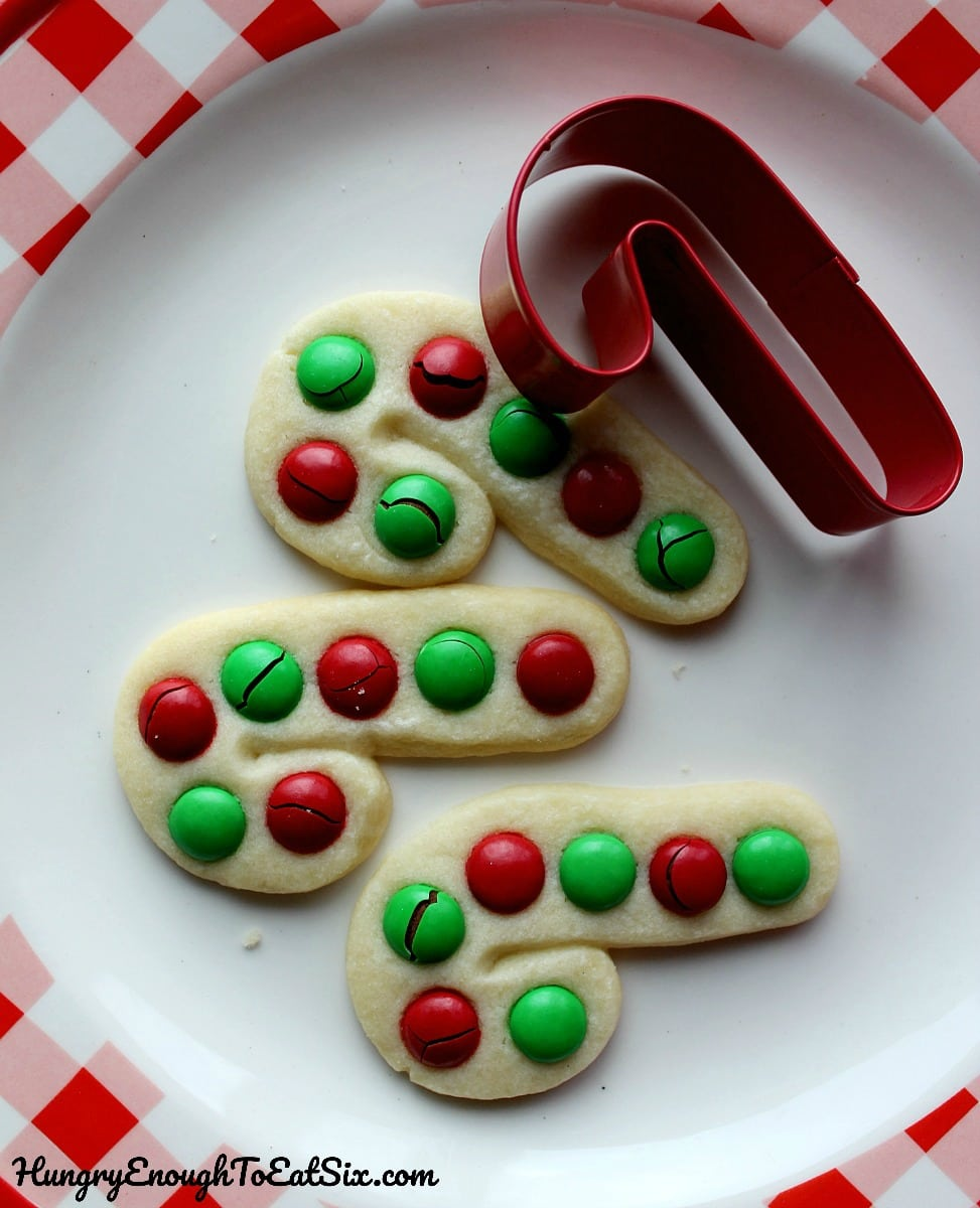 Three candy cane shaped cookies with red and green M&M's on a white plate.