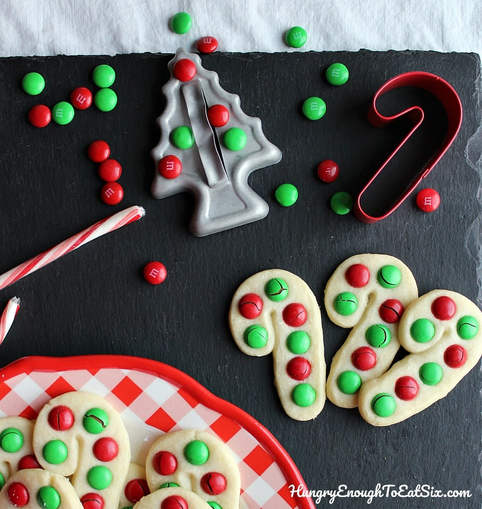 Candy cane shaped cookies with red and green M&M's on black slate background.