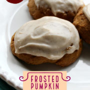 Blue and white plates holding frosted pumpkin cookies.