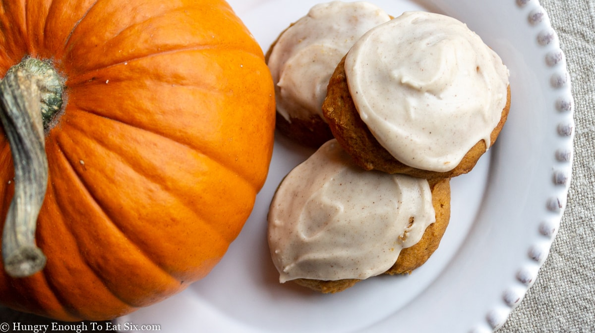 Three frosted cookies next to a pumpkin
