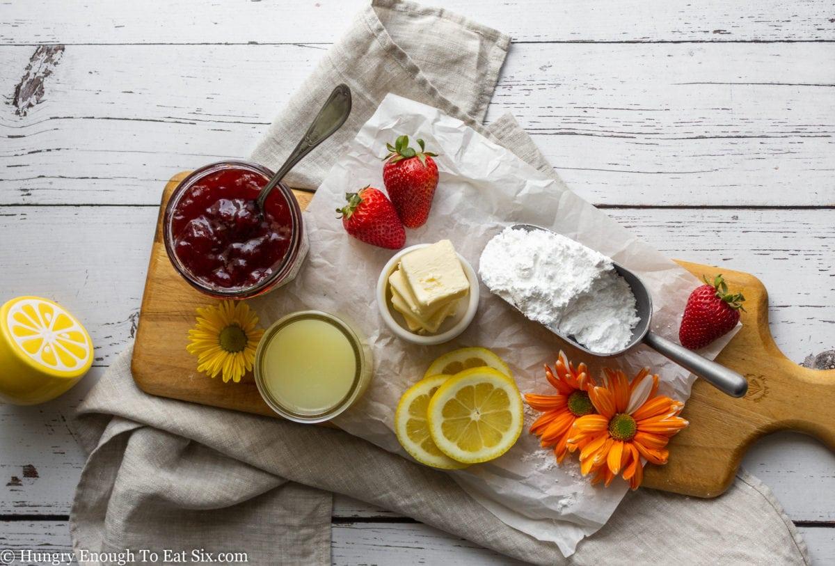 Butter, sugar, lemon juice and jam on a board