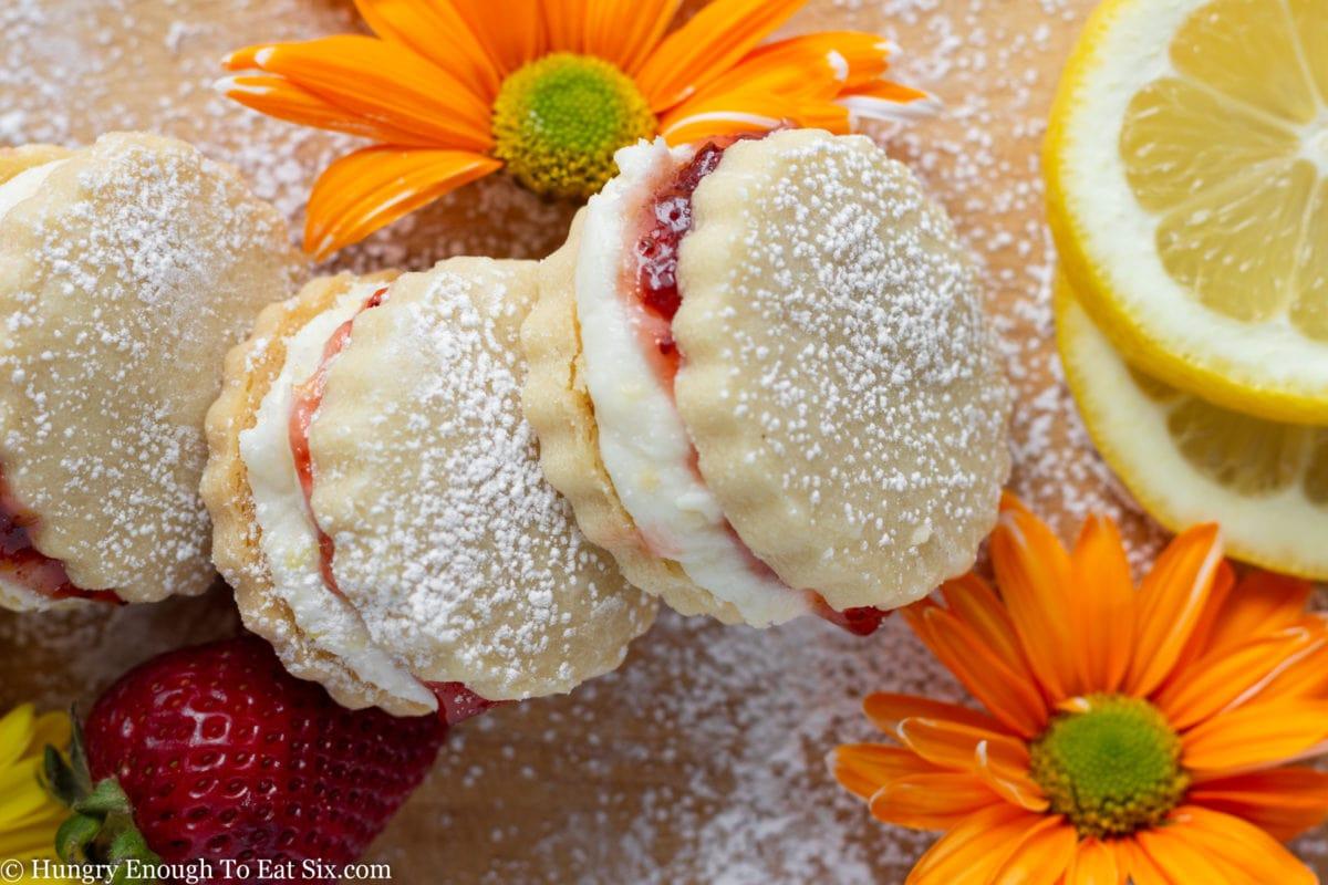 Cream and jam filled cookies near orange flowers
