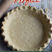 Pie shell with crimped edges and a rolling pin nearby