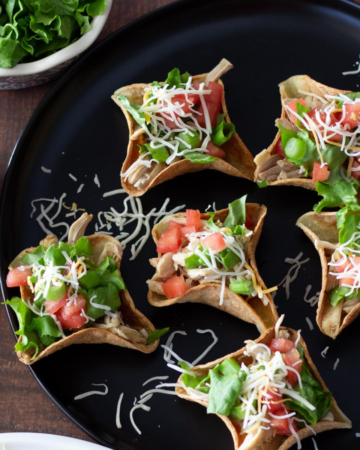 Chicken taco cups with toppings on a black dish.