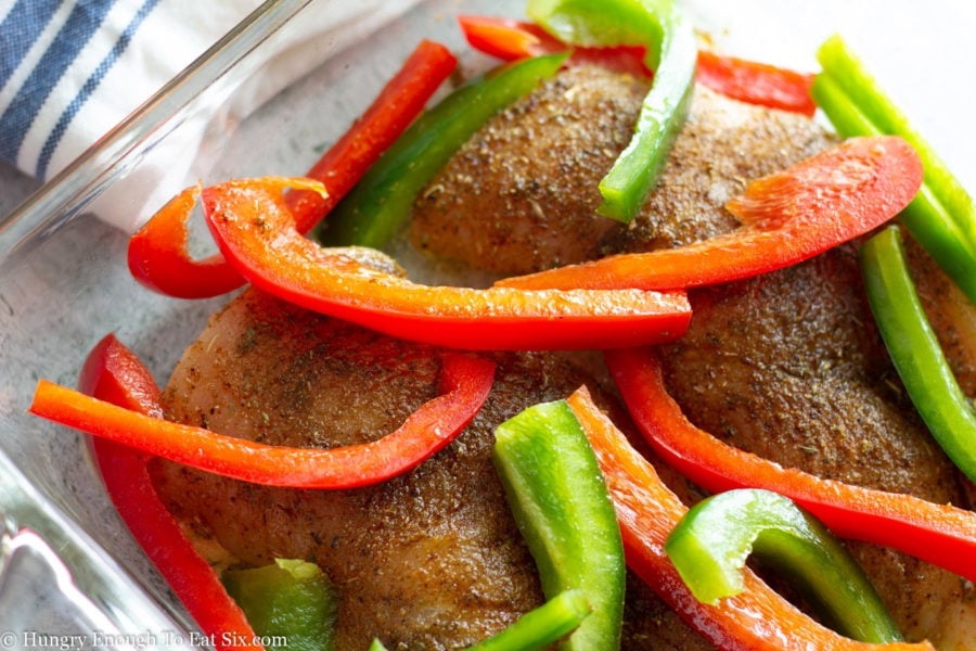 Chicken uncooked in baking dish with strips of bell pepper.