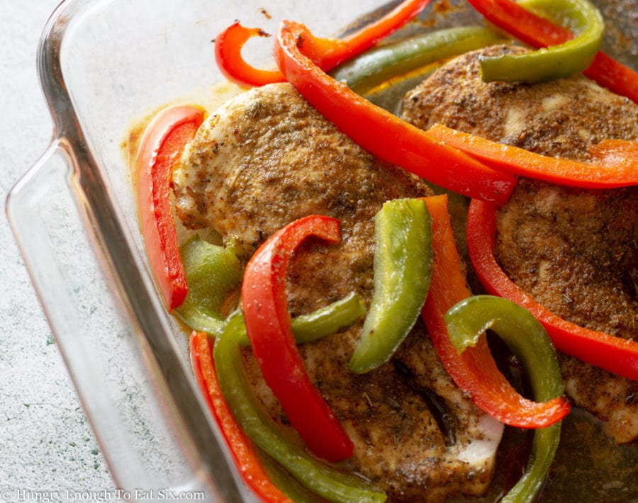 Baked chicken breasts with red and green pepper strips.