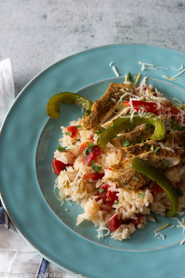 Mexican seasoned chicken breast strips with rice and peppers on a blue plate.