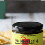 Jar of salsa verde with yellow label, tortilla chips behind.