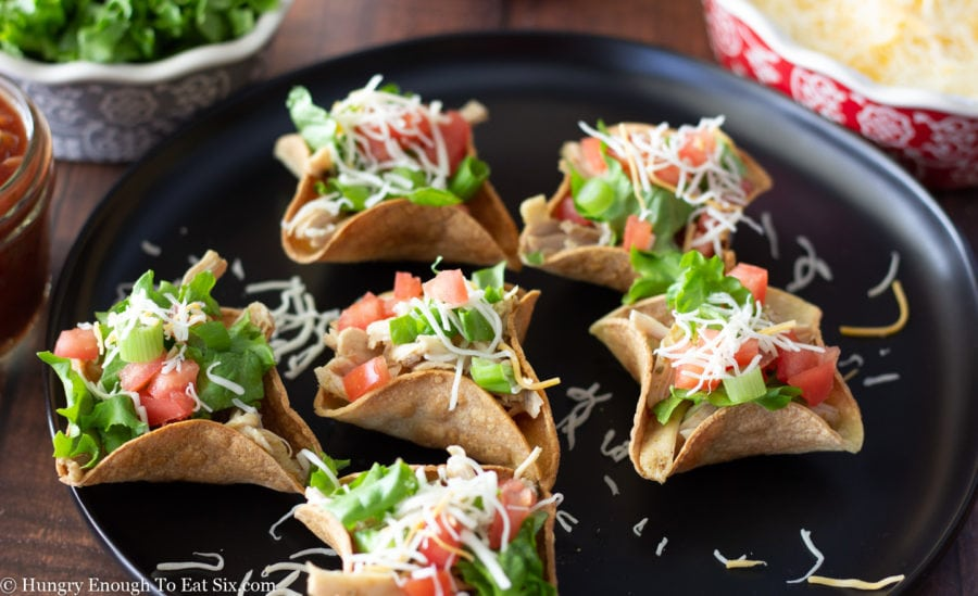 Taco cups with shredded chicken, tomato, scallions and cheese.