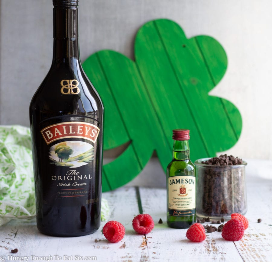Bottle of Baileys Irish Cream with a shamrock in background, berries in foreground.
