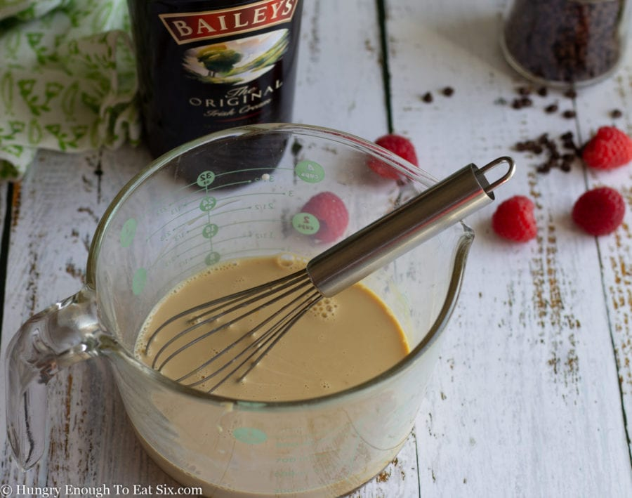 Baileys Irish Cream in a measuring cup with a whisk.