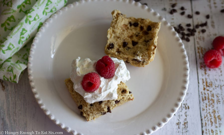 Chocolate chip scone split open with cream and raspberries