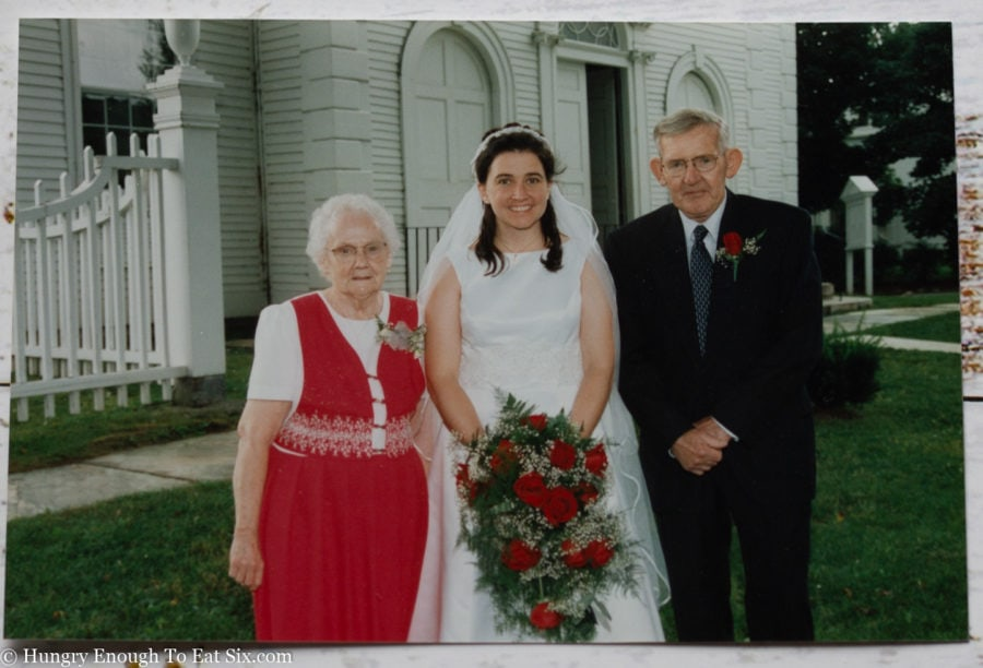 Wedding photo of bride with grandparents on either side.