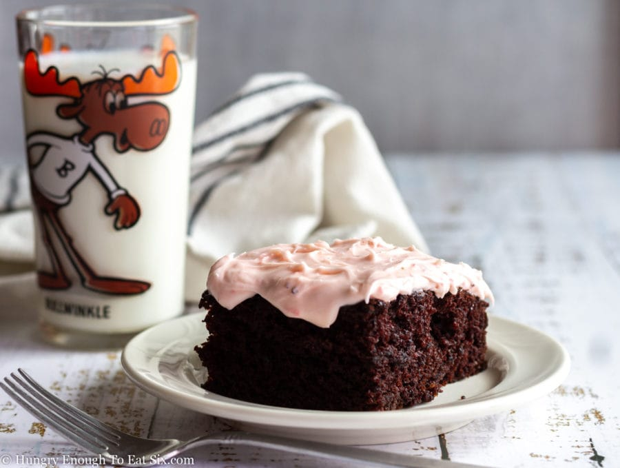 Chocolate cake with strawberry frosting on a white plate.
