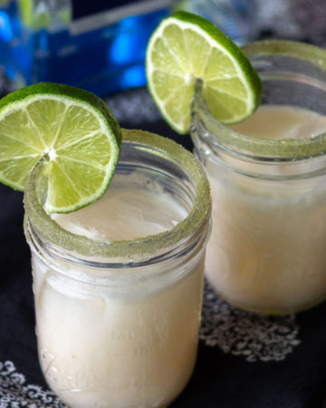 Coconut and lime margaritas in small mason jars with limes.