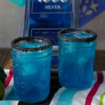 Two blue margaritas with black salt on the rims, tequila in background.