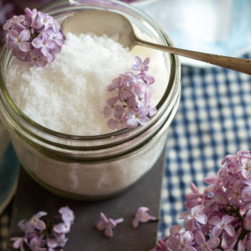 Glass dish holding lilac infused white sugar with lilac blooms acroos top.