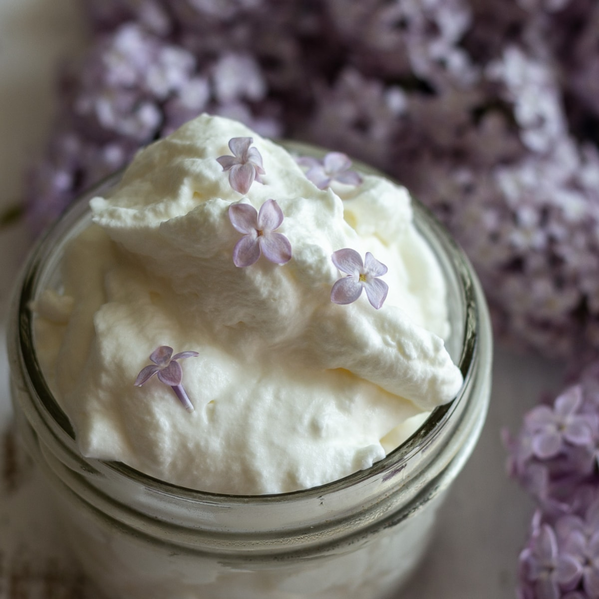 Small glass mason jar holding whipped cream with purple lilacs in background.
