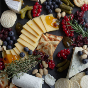 Slate cheese board laid with slices of cheese, crackers, berries, nuts and pickles.