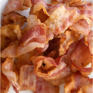 Pile of cooked bacon strips on a white plate.