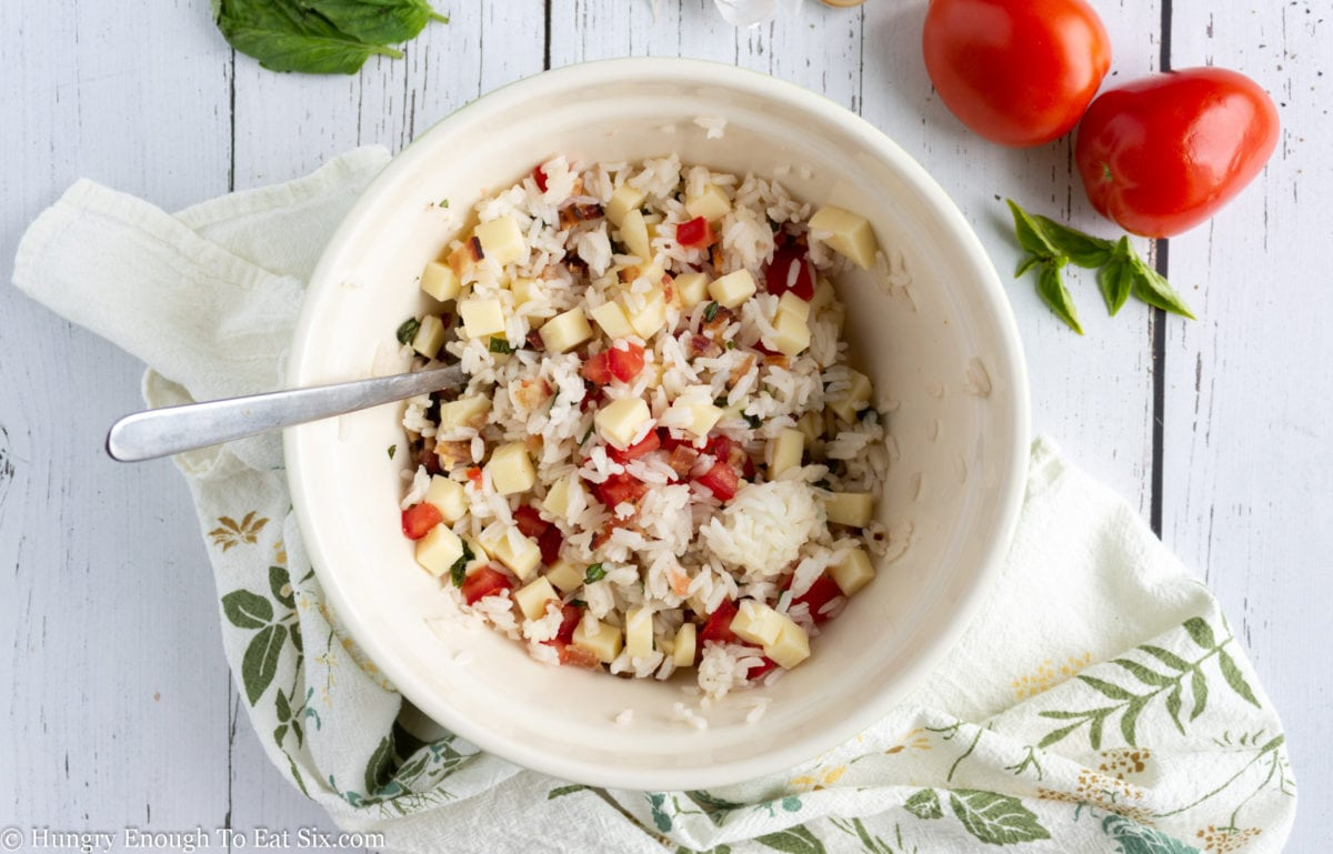White bowl holding rice, tomato and cheese cubes