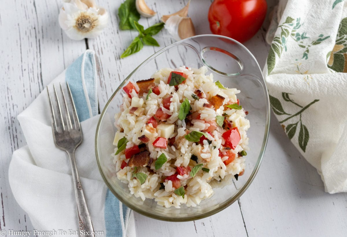 Glass bowl of rice salad near a fork
