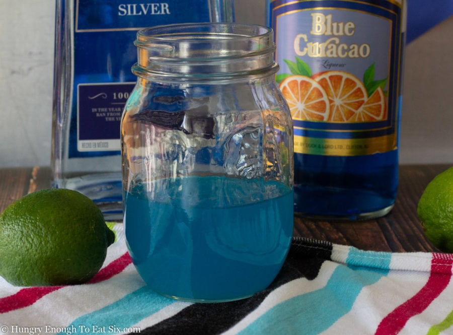 Blue margaritas mixture in a larger mason jar next to bottles of alcohol.