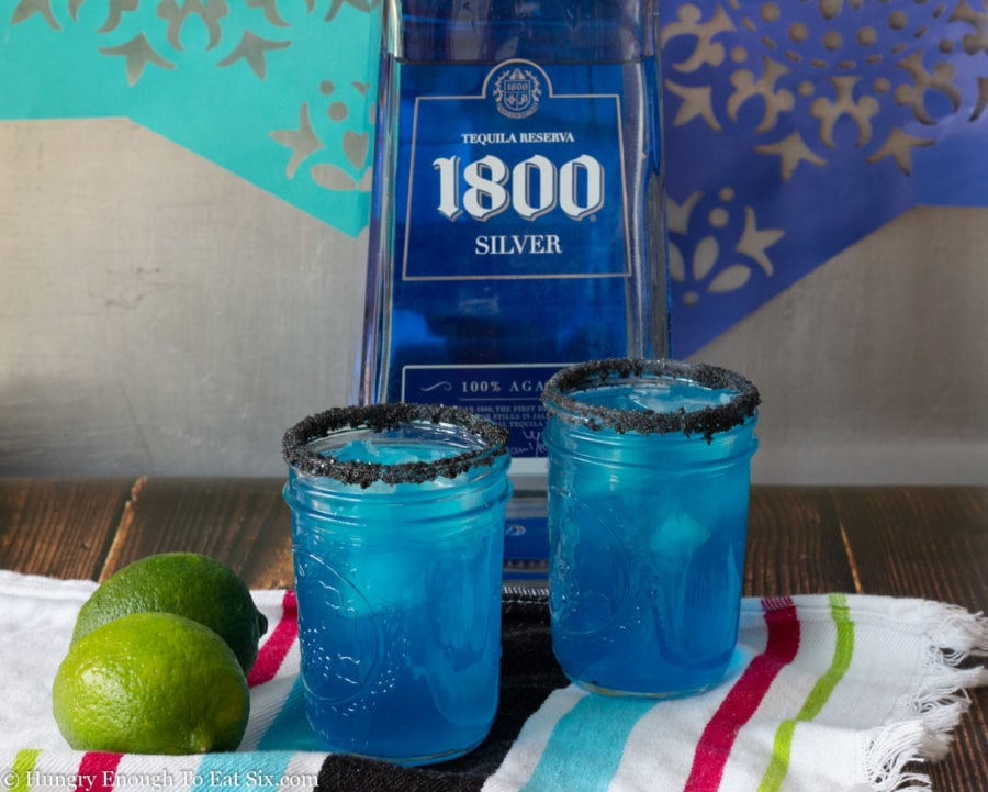 Two blue margaritas with black salt on the rims.