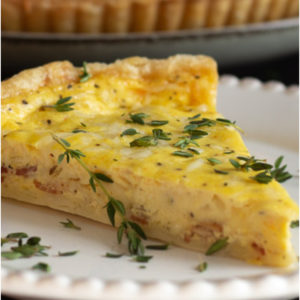 Slice of quiche Lorraine on a white plate.
