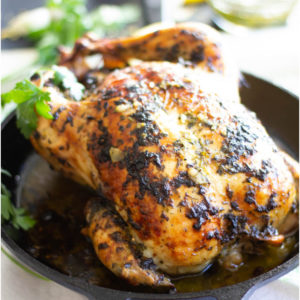 Whole roast chicken with a herb marinade in a cast iron skillet.
