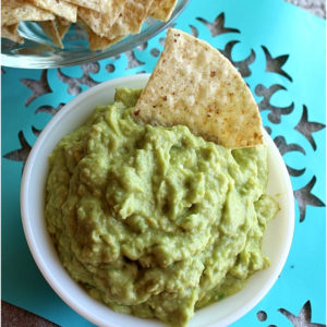 Bowl of guacamole with a tortilla chip, blue paper flag underneath.