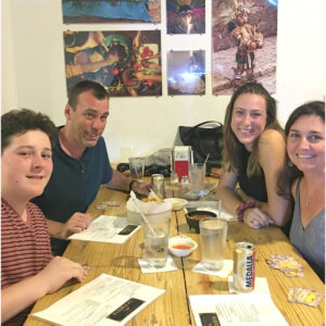 Family sitting at restaurant table in Puerto Rico, menus and drinks on table.