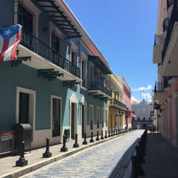 Cobblestone street lined with brightly painted buildings in Puerto Rico.