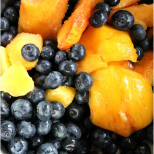 Bowl of blueberries with slices of fresh mango.