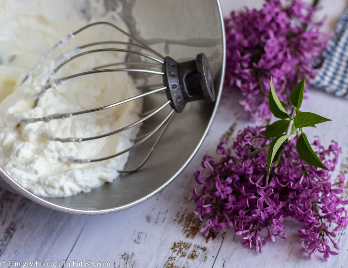 Mixer bowl and whisk attachment with whipped cream in the bowl, lilacs next to the bowl.